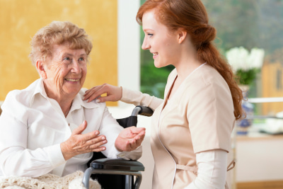 smiling elderly woman talking to a friendly caregiver in the nursing house