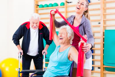 seniors in physical rehabilitation therapy with trainer